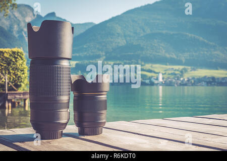 Digital camera lenses standing on wooden board with mountain landscape at background. Copy space background. Vintage filter - Stock Image