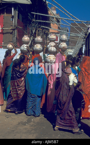 Indian women colorful dressed in sari and with presents on their head for a wedding in India Rajastan - Stock Image