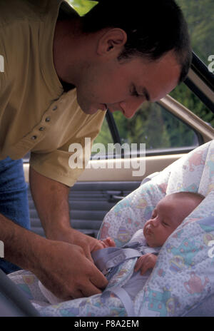 Father fastening baby into car seat - Stock Image