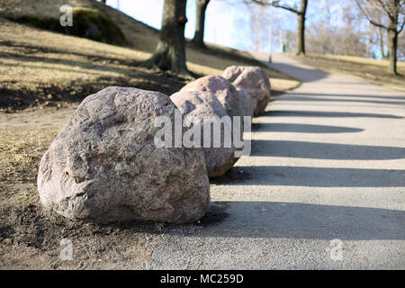 A walkway during spring after the snow has melted. Pale yet beautiful nature including some trees, grass and rocks. Beautiful sun light. - Stock Image