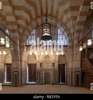 Marble wall with mihrab (Embedded niche), two wooden doors, huge arches, stained glass windows and chandelier at mosque attached to Khayer Bek Mausole - Stock Image