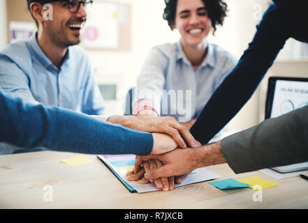 Group of unrecognizable young businesspeople sitting around table in a modern office, stacking hands. - Stock Image
