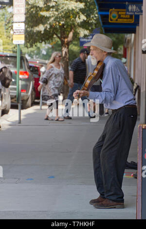 ASHEVILLE, NORTH CAROLINA, USA - September 9, 2018: An older violin player plays solo for tips on a busy downtown Asheville street on September 9, 201 - Stock Image