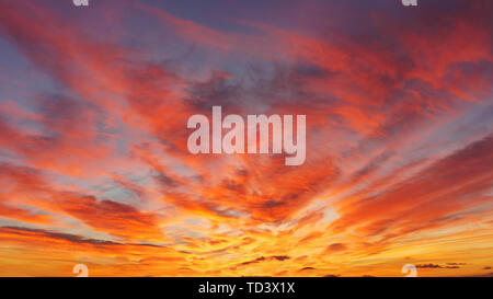 beautiful cloudscape at sunset with red clouds on sky - Stock Image