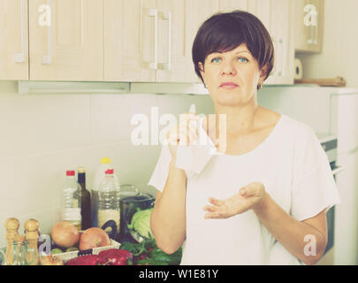 sad retiree woman holding napkin and standing against kitchen interior background - Stock Image