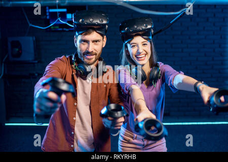 Portrait of a young couple standing together with virtual reality headsets and gamepads ready to play in the playing club - Stock Image