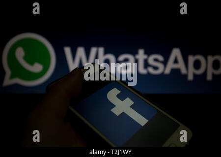 Facebook logo is shown on a smartphone display, WhatsApp logo unfocused on background - Stock Image