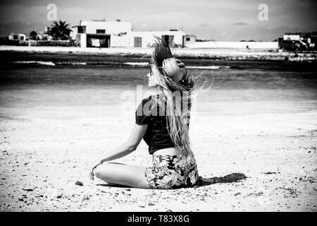 Black and white romantic and motivational portrait of beautiful blonde girl viewed from back sitting on the sand at the beach with sea and white house - Stock Image