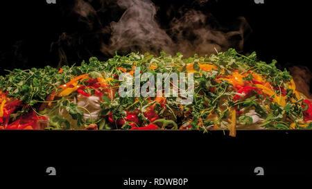 Stir-fry  on large rectangular hot metal plate displaying fresh vegetables and some smoke - chinese food - Stock Image
