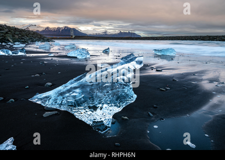 The stunningly beautiful Diamond Beach. Located The  by Jökulsárlón glacial lagoon in southeast Iceland. Chunks of iceberg wash up on this black lava  - Stock Image