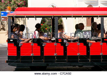 Tourists sightseeing in Rhodes Greece riding a red mini train looking at the sights - Stock Image