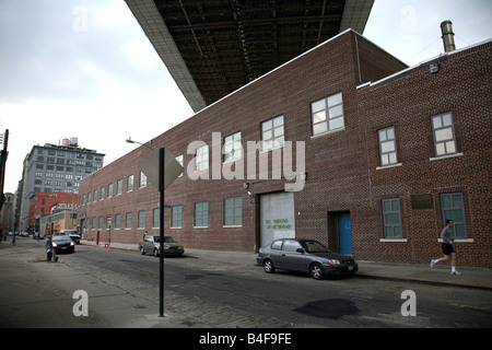 Man jogging past warehouse during the opening day of the New York Photo Festival, Dumbo, Brooklyn, NY, USA - Stock Image