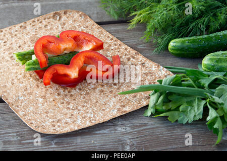 Pitta bread with green-stuff vegatables during summer barbecue with cutted red bell papers. Concept of healthy food - Stock Image