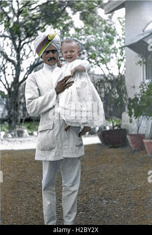 Colourised image showing an RAMC orderly holding Tom Frost, son of Lt.Col Austin Frost (RAMC) in the garden of their - Stock Image