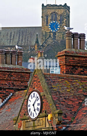 Just Gone Five! Scarborough's St Mary's Church and the town's West Pier buildings' clocks tell 2 seagulls what time it is. - Stock Image