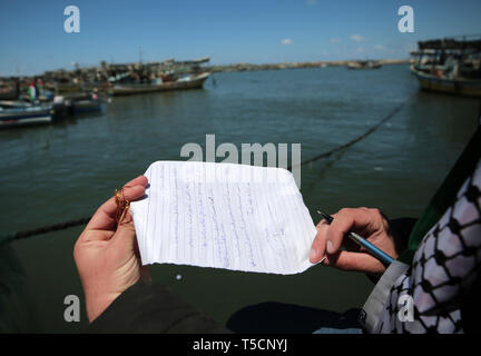Gaza. 22nd Apr, 2019. A Palestinian holds a letter before putting it into a bottle, at Gaza's fishing harbor in Gaza City, April 22, 2019. Dozens of Palestinian youths in Gaza City have sent letters to countries around the world, demanding solution to their problems and the lift of Israel's blockade on the Gaza Strip. These letters were written on Monday during an event held at Gaza's fishing harbor, before being sealed in small bottles and tossed into the sea. Credit: Yasser Qudih/Xinhua/Alamy Live News - Stock Image