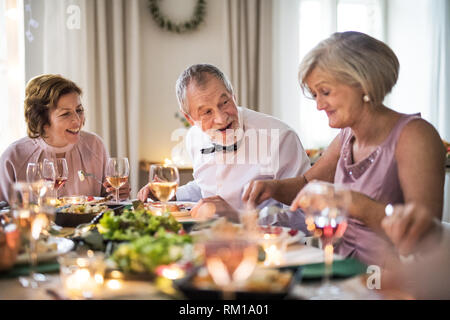 Seniors sitting at the table on a indoor family birthday party, eating. - Stock Image