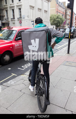 Male Deliveroo cyclist and Just Eat taxi come together on Southampton Row, Bloomsbury, London, UK - Stock Image