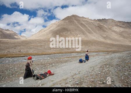 Group of Tibetan pilgrims circumambulating Mount Kailash by performing full body prostrations - Stock Image