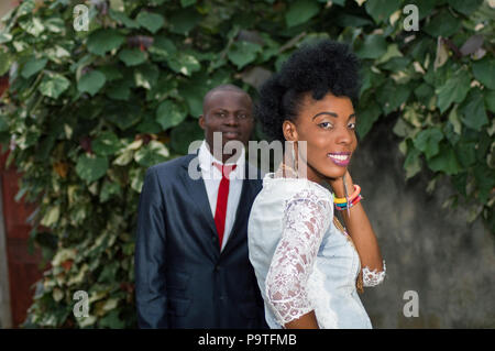 young smiling woman with hand in hair looking at the camera and in the background, a young man looking at her. - Stock Image