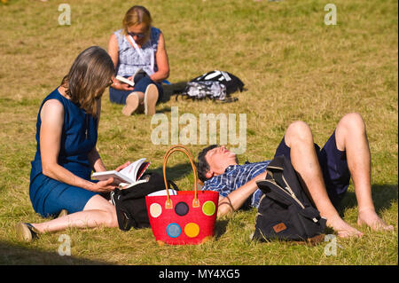 Women reading a books sitting on lawn in summer sunshine in garden area at Hay Festival 2018 Hay-on-Wye Powys Wales UK - Stock Image