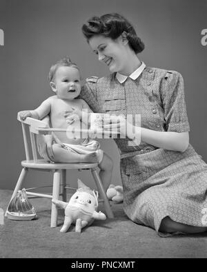 1940s SMILING MOTHER SUPPORTING ONE YEAR OLD BABY SON SITTING IN CHAIR AMONG VARIOUS TOYS - b12628 HAR001 HARS JUVENILE STYLE YOUNG ADULT BALANCE STRONG PLEASED JOY FEMALES LADIES PHYSICAL FITNESS PERSONS CARING B&W HAPPINESS WELLNESS CHEERFUL STYLES AMONG IN SMILES UPDO CONNECTION VICTORY ROLLS JOYFUL STYLISH VARIOUS BABY BOY PERSONAL ATTACHMENT SUPPORTING AFFECTION EMOTION FASHIONS GROWTH JUVENILES MOMS ONE YEAR OLD TOGETHERNESS YOUNG ADULT WOMAN BLACK AND WHITE CAUCASIAN ETHNICITY HAR001 OLD FASHIONED - Stock Image