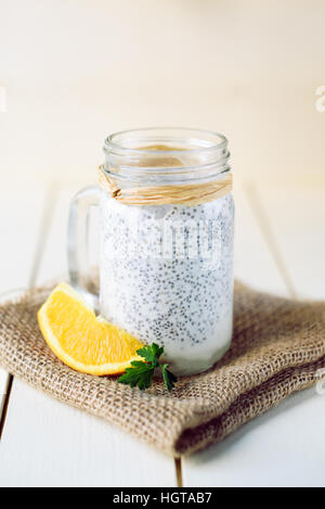 Chia seed pudding in a jar on white wooden background, decorated with orange and goji berries - Stock Image