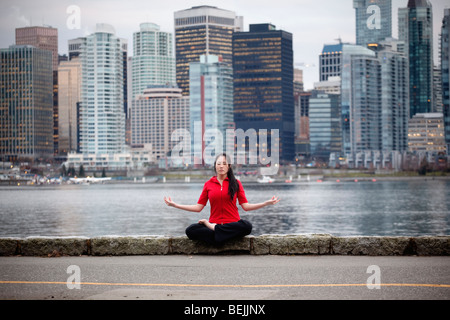 A young Asian woman doing yoga on the seawall at Stanley Park with the downtown skyline beyond, Vancouver, BC, Canada - Stock Image