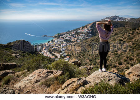Beautiful woman standing on a cliff with the mediterranean sea and small coast town in the background in Spain - Stock Image