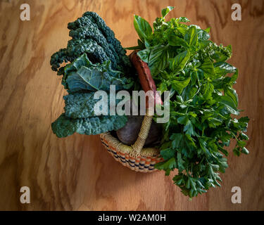 Closeup on organic, natural-looking vegetables and herbs  in the summer, in woven basket, on wooden background, viewed from the top and with some copy - Stock Image
