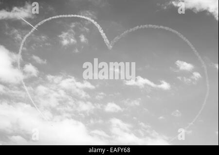 Red Arrows flying display at Malta International Airshow 2014, A Red Arrow pierces a heart - Stock Image