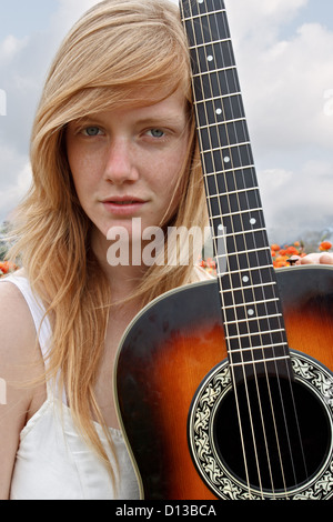A beautiful young lady is captured holding her acoustic guitar. - Stock Image