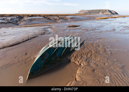 Mud flats at Uphill on the River Axe with a small boat sunk into the dangerous Severn estuary mud, Brean Down in the distance. - Stock Image