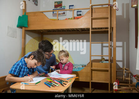 Brothers coloring with colored pencils while father is assisting them, Munich, Germany - Stock Image