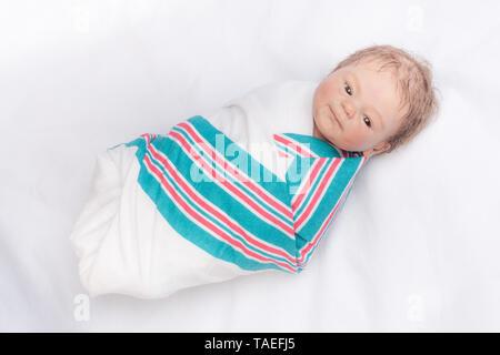 Newborn Reborn swaddled in a hospital blanket. Reborn baby doll. Vinyl sculpt, Coco Malu by Eliza Marx. - Stock Image