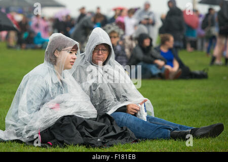 Portsmouth, UK. 29th August 2015. Victorious Festival - Saturday. Two women sit on the grass in ponchos protecting - Stock Image