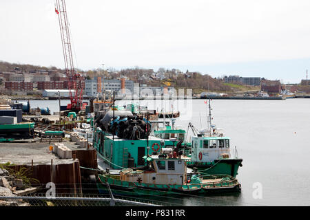 May 12, 2018 - Dartmouth, Nova Scotia: Along the Dartmouth waterfront, apartment buildings and industrial boats from Dominion Diving line the waterfro - Stock Image
