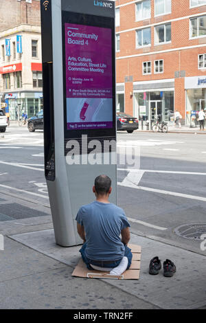 A Muslim food vendor takes a work break to say his daily prayers. On Eighth Ave in the Chelsea section of Manhattan, New York City. - Stock Image
