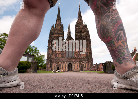 Unusual view of west front of Lichfield Cathedral seen through the tattooed well muscled legs of man wearing shorts - Stock Image
