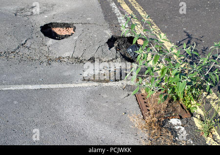 Potholes in tarmac carpark - Stock Image