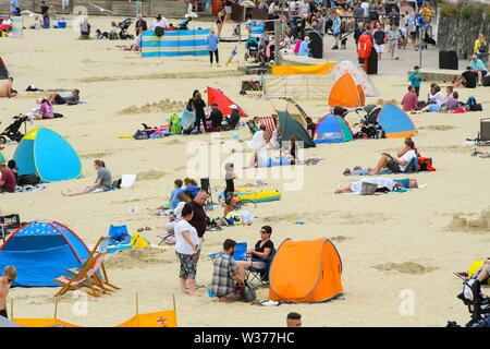 Lyme Regis, Dorset, UK.  13th July 2019. UK Weather.  Families on the beach enjoying themselves at the seaside resort of Lyme Regis in Dorset on a warm cloudy day.  Picture Credit: Graham Hunt/Alamy Live News - Stock Image