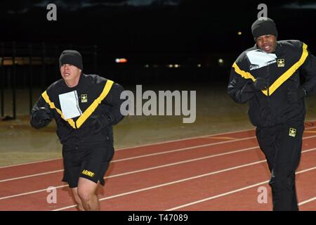 FORT BLISS, Texas – U.S. Army Soldiers run through the track for the 1,000 meter run/sprint event during the Basic Fitness Test of the German Armed Forces Badge for Military Proficiency at the Mitchell W. Stout Physical Fitness Center, Fort Bliss, Texas, March 13, 2019. - Stock Image