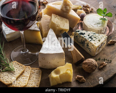 Cheese platter with organic cheeses, fruits, nuts and wine. Tasty cheese starter. - Stock Image