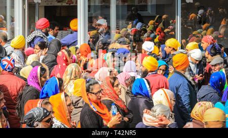 Gravesend, Kent, UK, 13th April 2019. Providing others with food and hospitality is integral to Sikh beliefs, and this local restaurant happily gives out snack and pizza to many of the visitors. Thousands of spectators and religious visitors line the streets of Gravesend in Kent to watch and participate in the annual Vaisakhi procession. Vaisakhi is celebrated by the Sikh community all over the world. - Stock Image