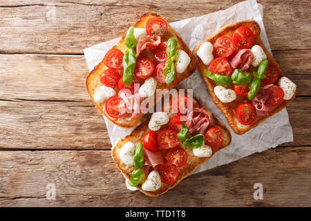 Delicious ciabatta with mozzarella, tomatoes, prosciutto and basil close-up on the table. Horizontal top view from above - Stock Image