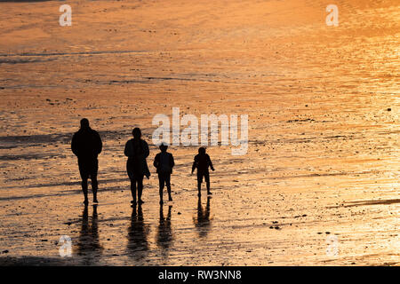 A family seen in silhouette walking across Fistral Bech at sunset in Newquay Cornwall. - Stock Image