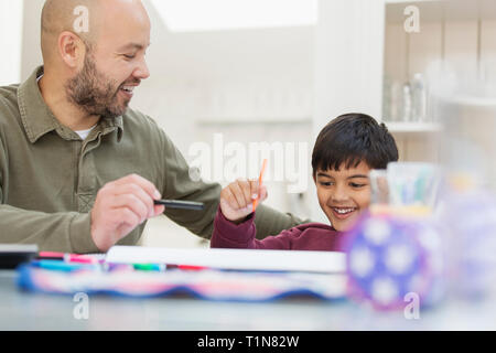 Father and son coloring at table - Stock Image