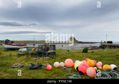Bright fishing bouys and lobster pots on shore at The Ouse bay on Holy Island with Lindisfarne Castle under renovation England UK - Stock Image