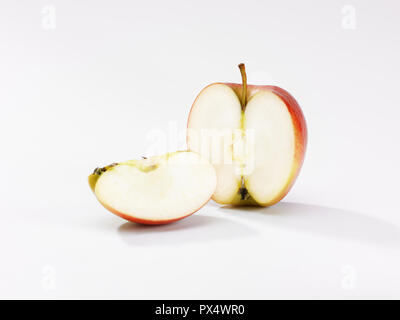 an apple sliced in half with a portion in front on a white background - Stock Image