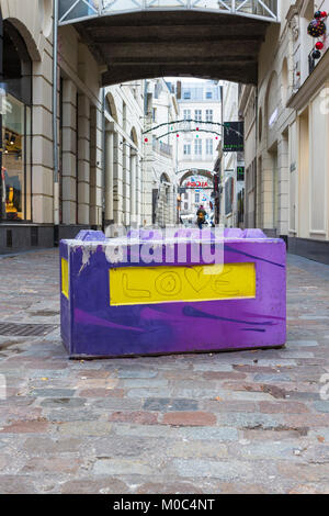 Concrete barrier with 'Love' painted on it in a shopping street in Lille, France - Stock Image